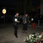 Két hölgy virágokat helyez az emlékműhöz