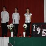 Ünnepi műsor a színpadon, három gyermek szaval