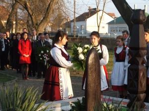 Március 15-i népviseletbe öltözött lányok koszorúznak